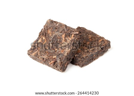 Two pressing briquette of black Chinese Shu Pu Erh tea isolated on white background, selective focus with shallow DOF - stock photo