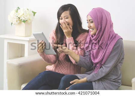 Two pretty asian women using tablet together at home - stock photo