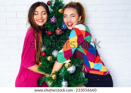 Two pretty best fiends girls posing near decorated Christmas tree, wearing bright party clothes, ready for celebration, smiling and have positive emotions before holidays. Cute indoor family portrait. - stock photo