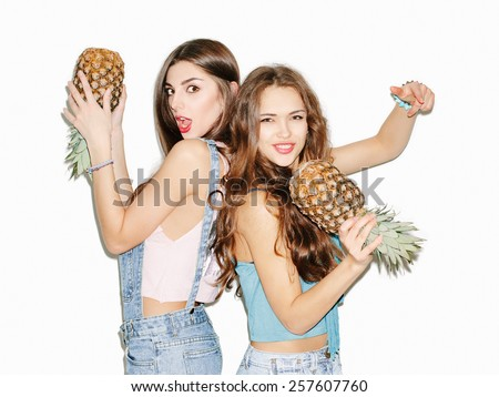 Two pretty brunette girl friends having fun with pineapple. Casual style, bright makeup, pink lips. White background, not isolated. Inside - stock photo