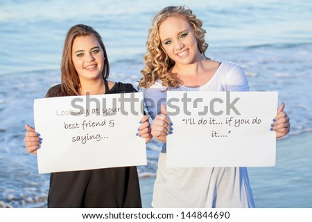 two pretty caucasian girls in contrast holding out a friendship quote smiling brightly with the ocean in the background - stock photo