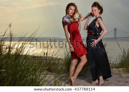 Two pretty Caucasian young fashionable women posing on the beach in luxury dresses. Horizontal photo. - stock photo