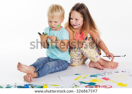 Two pretty child friends boy and girl are drawing pictures by aquarelle paints