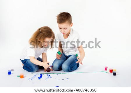 Two pretty child friends boy and girl in white shirts and blue jeans, trendy hair style, barefoot, drawing pictures on white sheet of paper by paints isolated on white. Studio shot. - stock photo