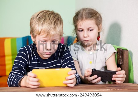 Two pretty children playing with cellphones - stock photo