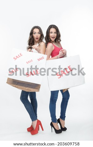 Two pretty dark-haired girls, coming from the mall standing with goods at cut rates. Isolated on the white background