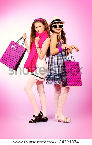 Two pretty fashion girls with shopping bags posing over pink background.  - stock photo