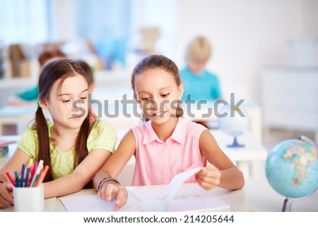 Two pretty friends discussing something in copybook at lesson - stock photo