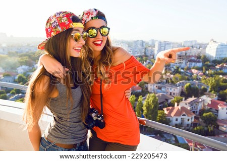 Two pretty girl posing on the roof, hugs and show something, have surprised positive emotions, sisters wearing bright stylish hipster swag clothes and sunglasses.