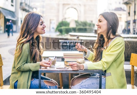 Two pretty girlfriends laughing while sitting in a bar outdoors - Students having pause and drinking cappuccino - Best friends talking and having fun - stock photo