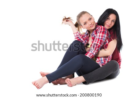 Two pretty girlfriends sitting on the floor. Isolated