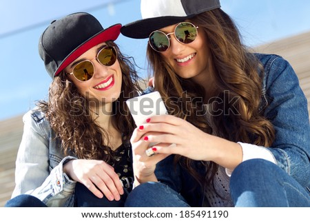 Two pretty girls having fun with smartphones - stock photo