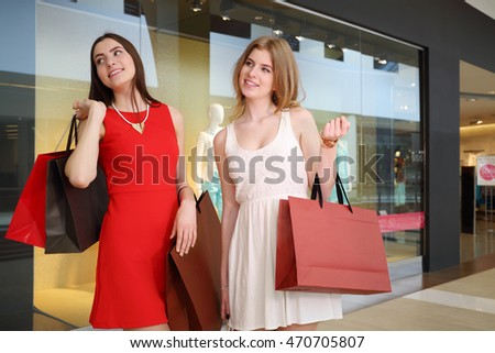 Two pretty girls in dresses with bags pose near showcase with mannequins