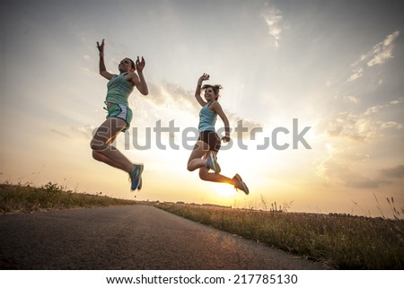 Two pretty girls jogging in the morning - stock photo