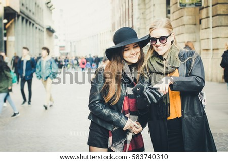 Two pretty girls looking at mobile phone, streets of Milan, Italy.