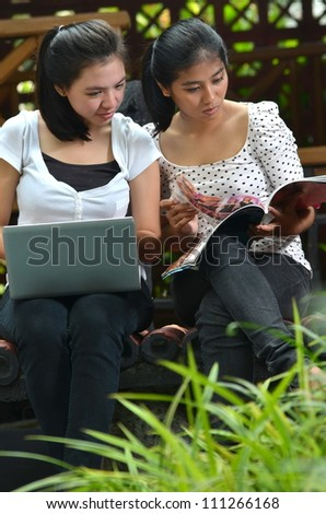 Two pretty girls (southeast asian) have fun studying, learning and sharing information they found on a laptop computer and a book or magazine at an outdoor scene.