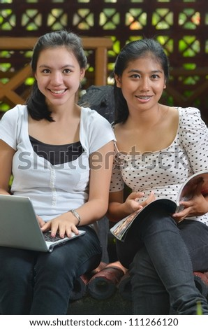 Two pretty girls (southeast asian) studying, learning and sharing information they found on a book/magazine at an outdoor scene.