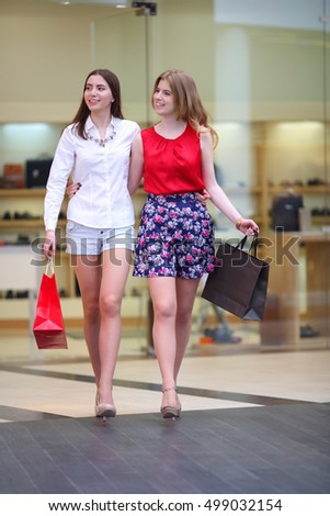 Two pretty girls with bags embrace and walk in big modern shop