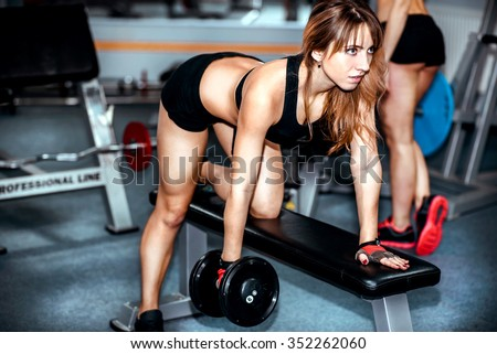 Two pretty girls workout in the gym - stock photo