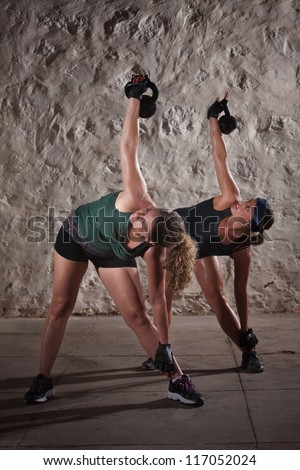 Two pretty ladies women lifting kettlebell weights over their shoulders - stock photo