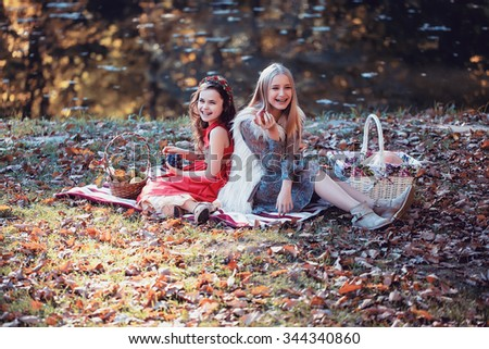 Two pretty laughing blonde and brunette girls in beautiful gowns with fruit in their hands and picnic baskets sitting on plaid on lake shore in autumn park, horizontal picture  - stock photo