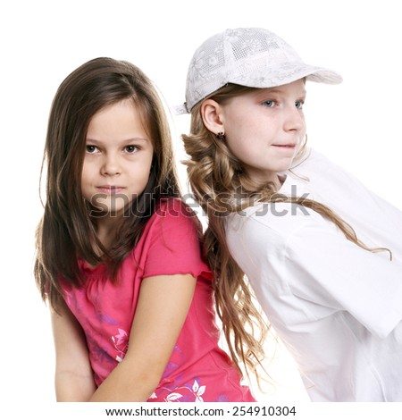 two pretty little girls playing in studio - stock photo