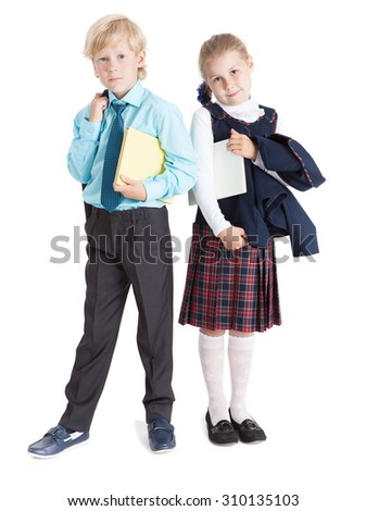 Two pretty pupils in school uniform stand full-length with books in hands, isolated on white background