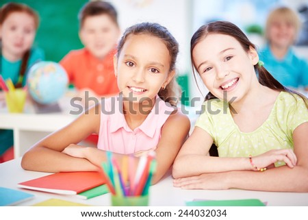 Two pretty schoolgirls looking at camera in classroom