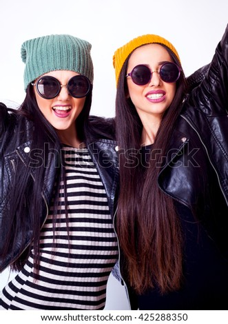 Two pretty sisters hipster girls hugs and having fun together, wearing trendy clothes, positive emotions, bright colors.Two young girlfriends in sunglasses having fun. Lifestyle.Hands rising up. - stock photo