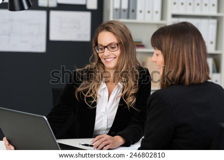 Two Pretty Smiling Businesswomen in Black Business Suits, Discussing the Business using Laptop Device. - stock photo