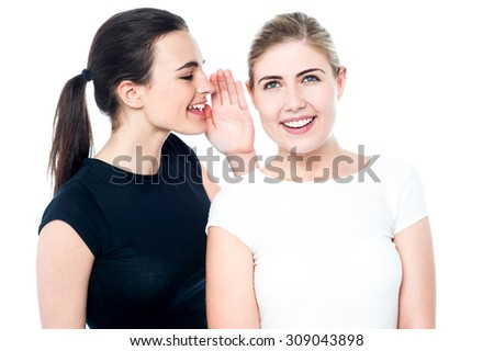 Two pretty smiling girls sharing a secret - stock photo