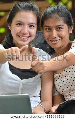 Two pretty southeast asian college girls with laptop posing a thumb with happy expression