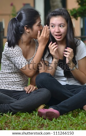 Two pretty southeast asian girls sharing exciting secret stories / gossiping  with happy expression at outdoor scene