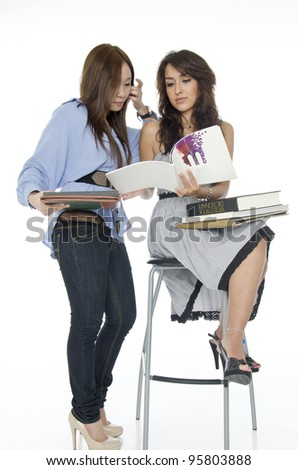 Two pretty university student girl sharing idea in study over white background.