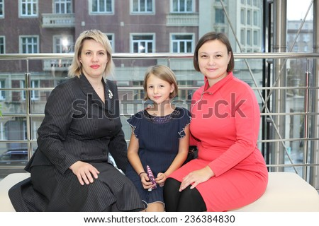 two pretty women and little girl in the waiting hall - stock photo