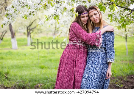 Two pretty women in long dresses - mother and daughter are walking and talking in the lush spring garden. - stock photo