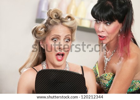 Two pretty women looking at a bad hairdo