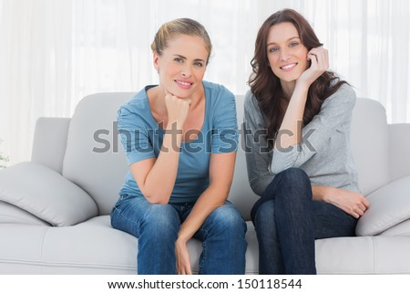 Two pretty women posing while sitting on the couch and looking at camera - stock photo
