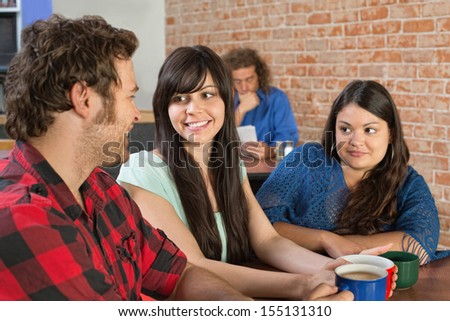 Two pretty women talking with man in cafe - stock photo