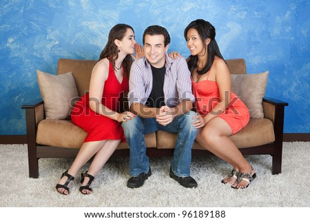 Two pretty women whisper and flirt with handsome man - stock photo