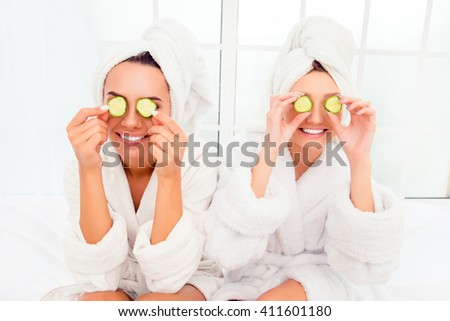 Two pretty women with cucumbers on eyes and towel on their heads - stock photo