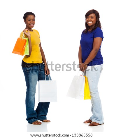 Two pretty, young African American friends with shopping bags on a white background - stock photo
