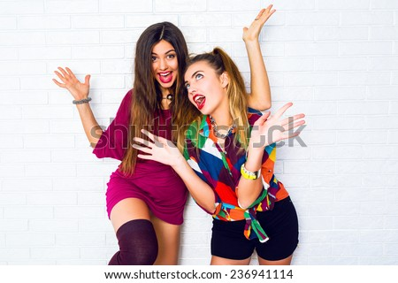 Two pretty young emotional women friends screaming and having fun together, wearing bright stylish casual clothes and bright make up. Urban white background. - stock photo