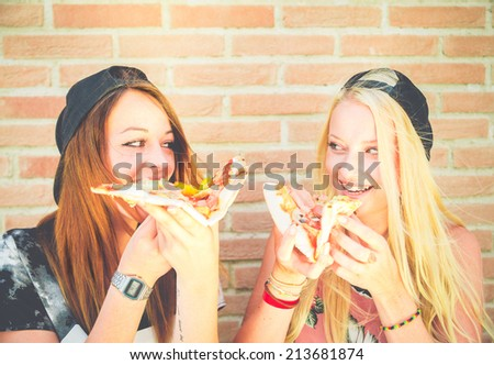 Two pretty young girls eating a slice of pizza - stock photo