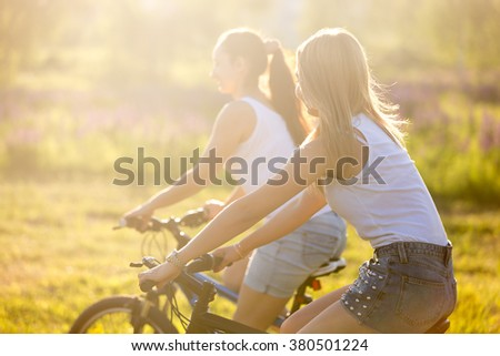Two pretty young happy beautiful girlfriends wearing casual white tank tops and denim shorts riding bikes in park in bright sunlight on summer day, back view - stock photo