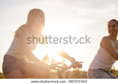 Two pretty young happy smiling beautiful girlfriends wearing casual white tank tops and jeans shorts riding bikes in park in bright sunlight on summer day, chatting together - stock photo