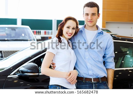 Two pretty young people smiling standing near car - stock photo