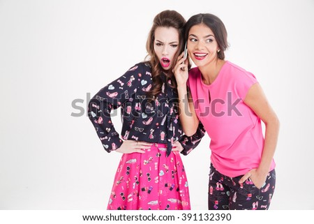 Two pretty young women listening conversation on cell phone over white background - stock photo