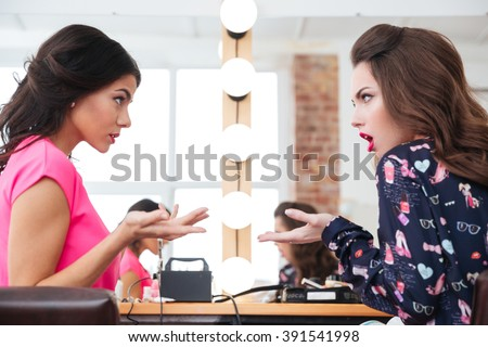 Two pretty young women sitting and arguing in beauty salon - stock photo