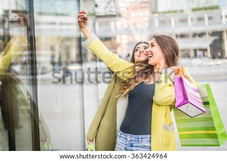 Two pretty young women taking a selfie while shopping - Girls buying some clothes in a shopping mall and having fun - stock photo